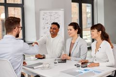 Recruiters having interview with employee. Job, hiring and employment concept - international team of recruiters having interview with male employee and shaking stock image