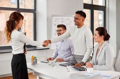 Recruiters having job interview with employee. New job, hiring and employment concept - international team of recruiters having interview and shaking hands with stock photos