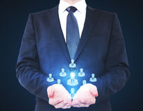 Recruiting concept. Businessman holding HR hologram on dark background. Recruiting concept Stock Photo