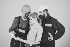 Recruitment concept. Brigade of workers, builders in helmets, repairers and lady discussing contract, grey background. Brigadier, foreman speak about results of Stock Photo