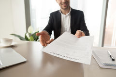 Recruitment manager offers employment agreement. Recruitment manager reaching out sheet with employment agreement. Smiling CEO offers to read and check work royalty free stock photo