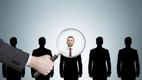 Recruitment process. Large human hand with magnifying glass examining man silhouettes against light gray wall. Concept of recruitment. Mockup royalty free stock photo