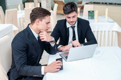 Recruitment. Two successful and confident businessman sitting at. The table in a business office in full costume in the office and working at a laptop and Stock Photo