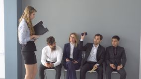 Recruits waiting for interviews for employment. a group of young businessman waiting for the start of the reception. Sitting on chairs in the lobby of an office Stock Photos