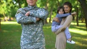 Recruta americano no uniforme militar com esposa e filho atrás, defesa da família filme