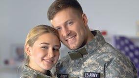 Recruta feliz e mulher novos que olham a câmera, par militar, exército americano filme