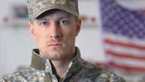 Recruta seguro que olha a câmera, bandeira nacional no fundo, exército americano filme