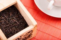 Rectángulo con té negro en la estera roja Imágenes de archivo libres de regalías