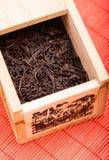 Rectángulo con té negro en la estera roja Imagen de archivo