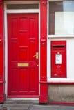 Rectángulo de carta rojo inglés al lado de una puerta roja Fotos de archivo libres de regalías