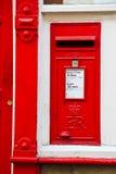Rectángulo de carta rojo inglés al lado de una puerta roja Fotos de archivo