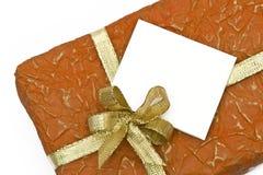 Rectángulo de regalo anaranjado y tarjeta congratulatoria Foto de archivo