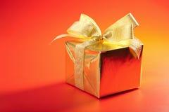 Rectángulo de regalo de oro con el arqueamiento sobre rojo Foto de archivo