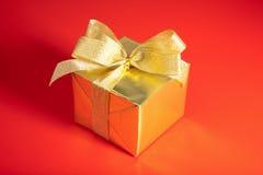 Rectángulo de regalo de oro con el arqueamiento sobre rojo Foto de archivo libre de regalías