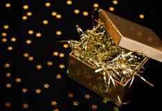 Rectángulo de regalo de oro en fondo negro Fotografía de archivo