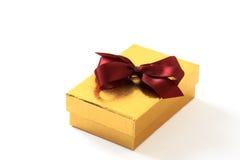 Rectángulo de regalo del oro con el arqueamiento rojo Fotografía de archivo libre de regalías