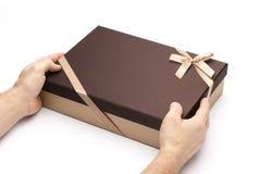 Rectángulo de regalo en manos en un fondo blanco. Fotos de archivo libres de regalías