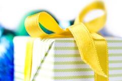 Rectángulo de regalo hermoso con la cinta amarilla sobre blanco Fotos de archivo