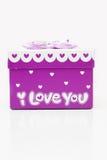 Rectángulo de regalo mano-púrpura hermoso en el fondo blanco Fotos de archivo