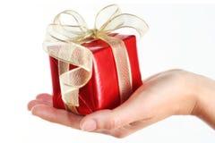 Rectángulo de regalo rojo en la mano de la mujer Fotografía de archivo