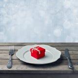 Rectángulo de regalo rojo en la placa con la fork y el cuchillo Imágenes de archivo libres de regalías