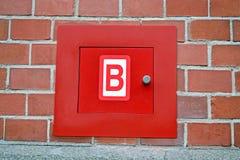Rectángulo del fuego rojo para la boca de riego, pared de ladrillo roja, seguridad moderna, Imagen de archivo