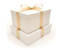 Rectángulos de regalo blancos empilados con la cinta del oro aislada Fotografía de archivo