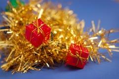 Rectángulos de regalo en la guirnalda del oro Foto de archivo