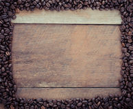 Rectangle frame made of coffee beans on the wooden background. Stock Photo