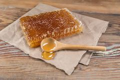 Rectangle Honey Comb and Wooden Spoon of Honey. Sit on Wooden Table Stock Photo