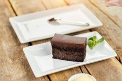 Rectangle Piece of Belgian chocolate cake. Piece of black cake on white plate. Rectangle plate with dessert Royalty Free Stock Image