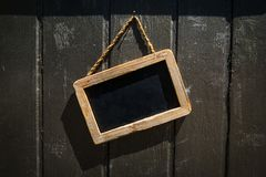Rectangular Blackboard Shop Sign with Wooden Frame on a Wood Wal stock images
