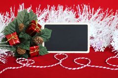 Rectangular blank slate to write a message, leaves filled with red gifts, a frosted white wreath and a red and white thread for Royalty Free Stock Images