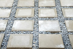 Rectangular concrete flagstone. Is selected focus at left and above of the frame,with other flagstones and strew around each flagstone by stones Royalty Free Stock Photography