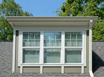 Rectangular Dormer Window. A dormer window on the roof of a newly constructed house.  It has blinds on the inside and gutters on the exterior Royalty Free Stock Photos