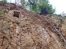 The rectangular entrance to Etruscan tombs carved in the wall of a tufo cliff. Etruscan tomb carved into the wall of a tufo cliff in Tuscany near an Etruscan stock images