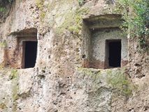 The rectangular entrances to Etruscan tombs carved in the wall of a tufo cliff. Etruscan tombs carved into the wall of a tufo cliff in Tuscany near an Etruscan royalty free stock photography