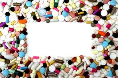 Rectangular frame of colorful pills on white background. Rectangular frame of assorted pills, capsules, caplets and tablets on white background. Vertical or Stock Images