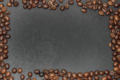 Rectangular frame made from fried brown coffee beans on a dark gray background. Royalty Free Stock Image
