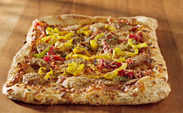 Rectangular gourmet pizza with sausage and colorfu Stock Photography