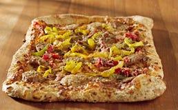 Rectangular gourmet pizza with sausage and colorfu Stock Photography