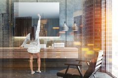 Rectangular mirror bathroom sink, armchair, woman. Woman standing near white angular sink standing on wooden countertop with a horizontal mirror hanging above it stock photo