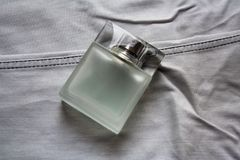 Rectangular perfume bottle on light grey jeans royalty free stock photography