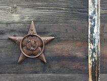 Rectangular horizontal photo background of a rustic bronze star on old weathered barn wood stock image