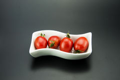 Rectangular plates in the small red tomatoes Royalty Free Stock Image