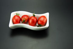 Rectangular plates in the small red tomatoes Stock Images