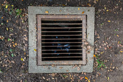 Rectangular sewer with a rust and holes. On the soil and grass background Stock Photo