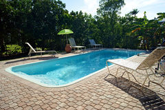Rectangular swimming pool with deck chairs Stock Images