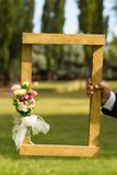 Rectangular wooden frame with a floral ornament held by a man`s hand stock photos