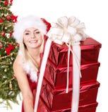 Rectángulo de regalo de la pila de la muchacha por el árbol de navidad. Foto de archivo
